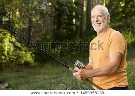 The fisherman looks at the caught fish Stock photo © galitskaya