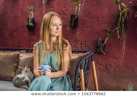 Young woman having a mediterranean breakfast seated at sofa and with her cat and drinks Trendy drink Stock photo © galitskaya