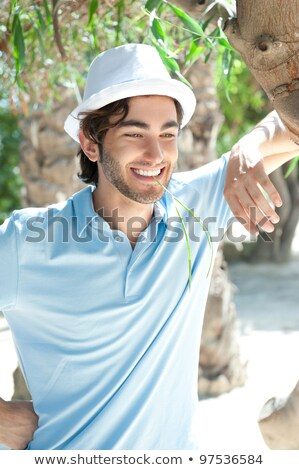 Young man wearing hat and casual clothes in sunny day. Leaning o Stock photo © HASLOO