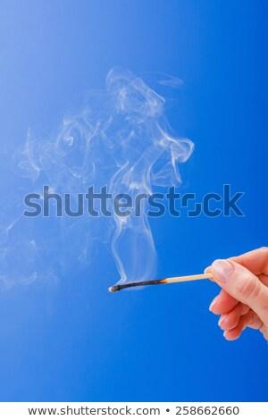 Hand holding burnt fuming matchstick Stock photo © erierika