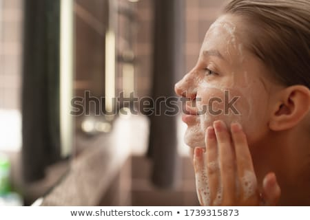 Stock photo: Woman From Shower Looking her Face at the Mirror