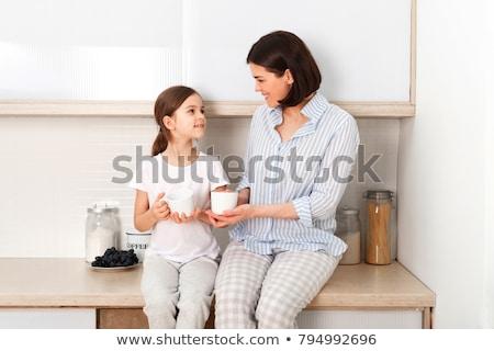 Mom and daughter drink something with mug Stock photo © tekso