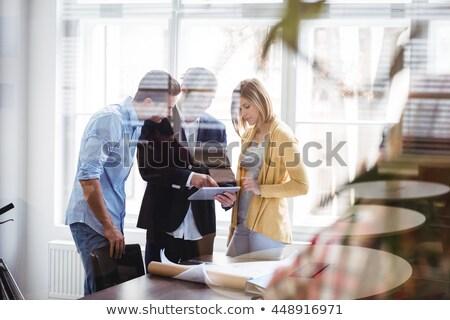 Businesswoman explaining to colleagues seen through glass Stock photo © wavebreak_media