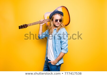 portrait of young blond man holding guitar on shoulder stock photo © feedough