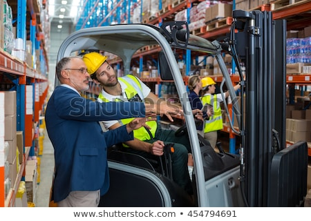 businessman and worker on forklift at warehouse stock photo © dolgachov