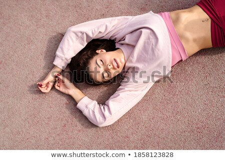 Portrait of a happy young fitness girl laying on a mat Stock photo © deandrobot