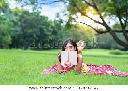 smiling young asian girl outdoors in park reading book stock photo © deandrobot