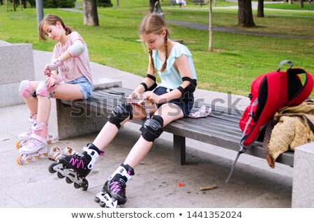 Two girls friends sisters on rollers sitting in park outdoors holding flag USA. Stock photo © deandrobot