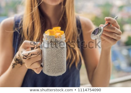 Young woman with mehendi from henna on hand eating chia pudding on her balcony overlooking the big c Stock photo © galitskaya
