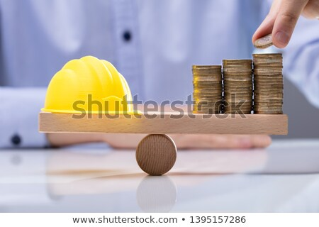 Yellow Hard Hat And Stack Of Coins On Seesaw Stock photo © AndreyPopov