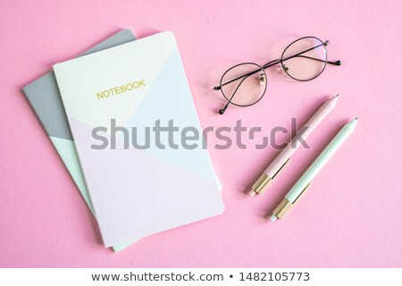 Top view of business person eyeglasses, two notebooks and pens Stock photo © pressmaster
