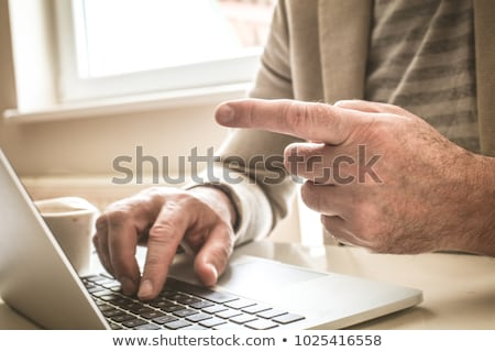 Close up of business man hand working on laptop computer with bu stock photo © Freedomz