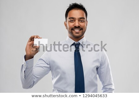 indian businessman with business card over office stock photo © dolgachov