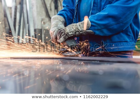 worker in metal factory grinding workpiece with sparks flying stock photo © kzenon