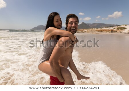 Side view of man giving woman piggyback ride and having fun at beach in the sunshine Stock photo © wavebreak_media