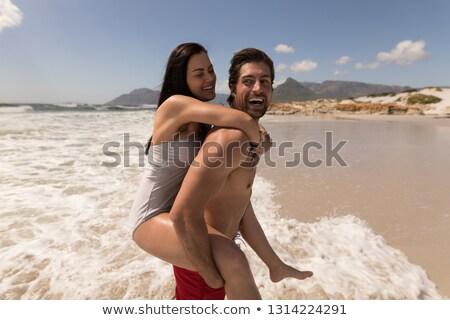 側面図 男 女性 ピギーバック ビーチ ストックフォト © wavebreak_media