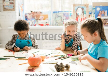 cute schoolgirl looking at one of classmates drawing face on dry leaf at lesson stock photo © pressmaster
