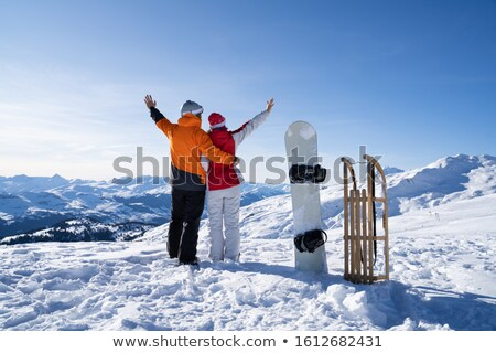 Happy Young Couple Standing Near Snowboard And Sledge In Snow Stock photo © AndreyPopov