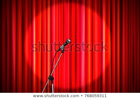 Red curtain with shiny microphone in round spotlight lighting, retro theater stage wide background Stock photo © evgeny89