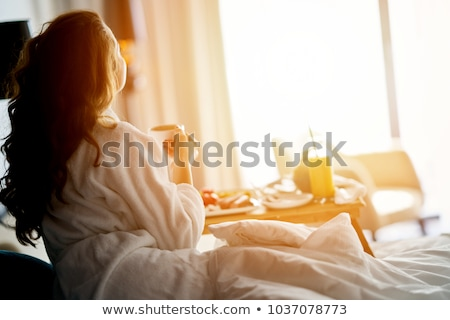 smiling woman drinking a coffee lying on a bed at home or hotel stock photo © hasloo