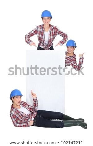 Tradeswomen surrounding a blank sign Stock photo © photography33