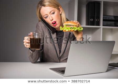Woman eating a hamburger while talking on the phone Stock photo © photography33
