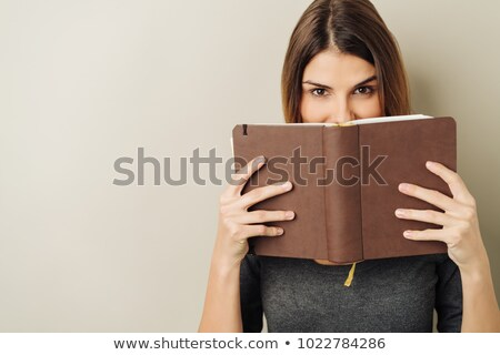 Smiling girl reading a book against a white background Stock photo © wavebreak_media