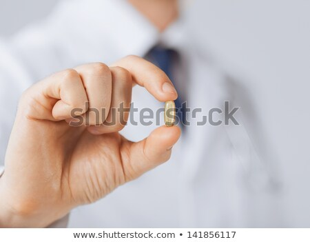 doctor hand showing one capsule Stock photo © dolgachov