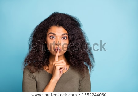 Young woman holds a finger to her mouth Stock photo © w20er