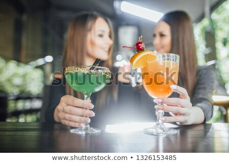 Beautiful girl in green dress with cocktail on summer terrace  Stock photo © Nejron