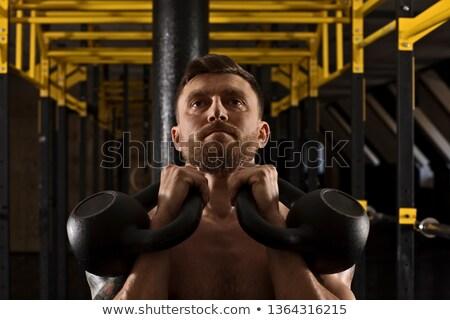 Focused bodybuilder lifting up kettlebells looking at camera Stock photo © wavebreak_media