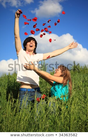 young pair scatters petals of roses in grass stock photo © paha_l