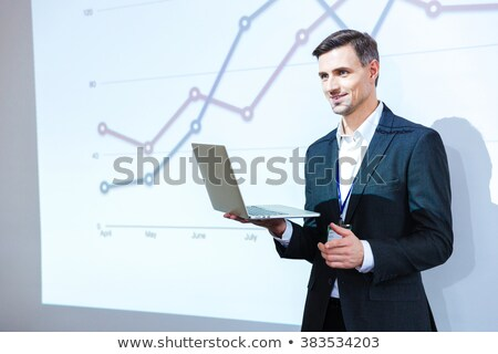 Smiling speaker standing and explaining graphs on business conference  Stock photo © deandrobot