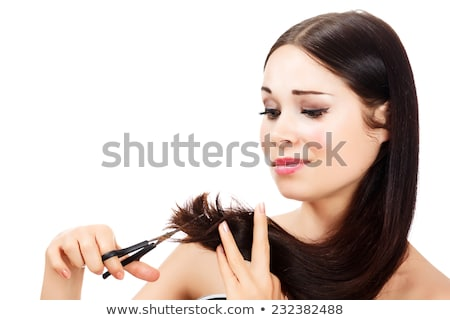 Serious woman cutting splitting ends of her long fragile hair Stock photo © deandrobot