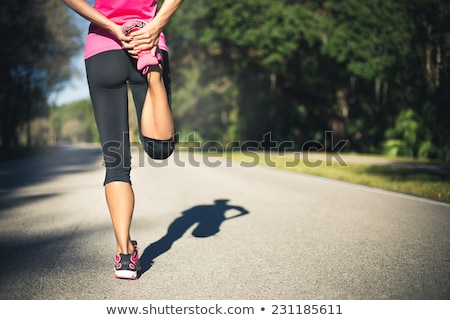 back view of young woman athlete standing and stretching legs stock photo © deandrobot