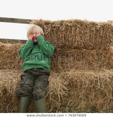 Stock photo: Boy hiding eyes on hay bales