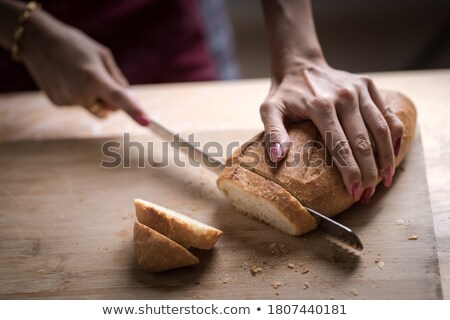 woman in bakery putting bread on board stock photo © kzenon