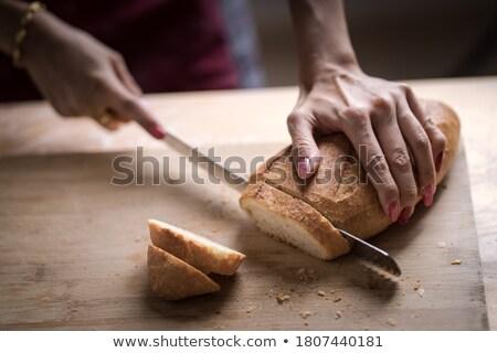 Woman in bakery putting bread on board Stock photo © Kzenon