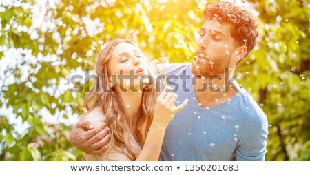 Young couple daydreaming about their future blowing dandelion seeds Stock photo © Kzenon