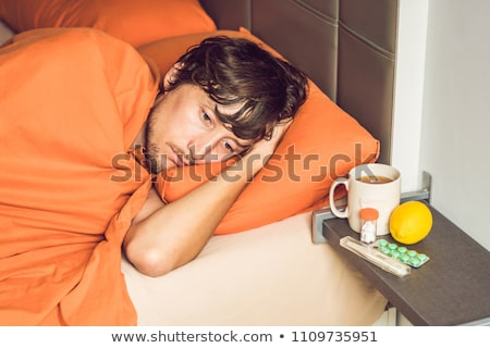Man feeling cold, lying in the bed and drinks tea and measures temperature with a thermometer Stock photo © galitskaya