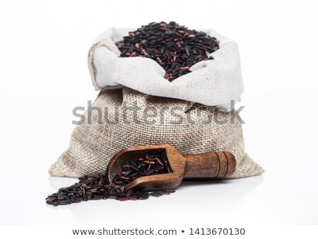 Wooden spoon and linen bag of raw organic black venus rice on white background.Healthy food.  stock photo © DenisMArt
