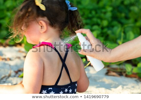 Stock photo: Woman Spraying Lotion On Her Daughter's Back