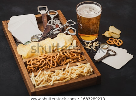 Glass and bottle of craft lager beer and opener with box of snacks on wooden background. Pretzel and Stock photo © DenisMArt
