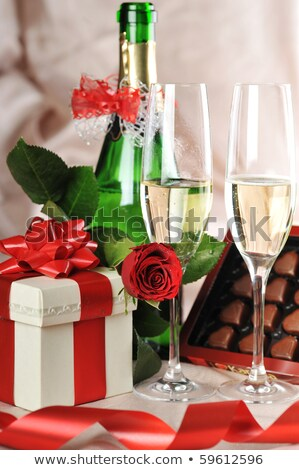 close up of champagne gift candies and red roses stock photo © dolgachov