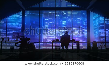 Silhouette of a videographer in the studio opposite a large business center. Stock photo © ConceptCafe