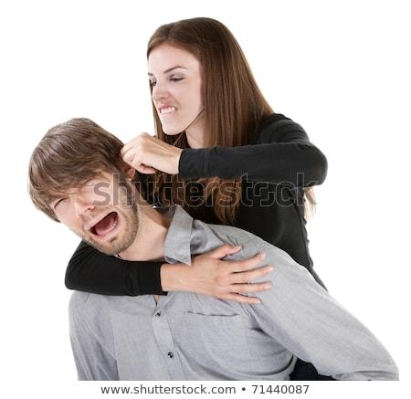 Beautiful Caucasian woman twisting boyfriend's ear while he scre Stock photo © dacasdo