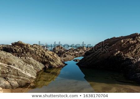 Sea, rock and distant fishermen Stock photo © trala