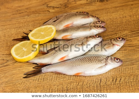 Stock photo: Fresh fishes with lemon.