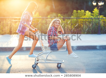 Two happy beautiful teen girls driving shopping cart outdoors Stock photo © vlad_star