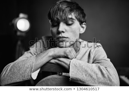 man in business suit looking down in studio with spotlights on Stock photo © feedough
